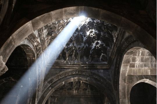 A shaft of light illuminates the interior of geghard Monastery