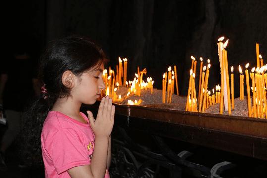 A young girl prayers in Geghard Monastery, Armenia