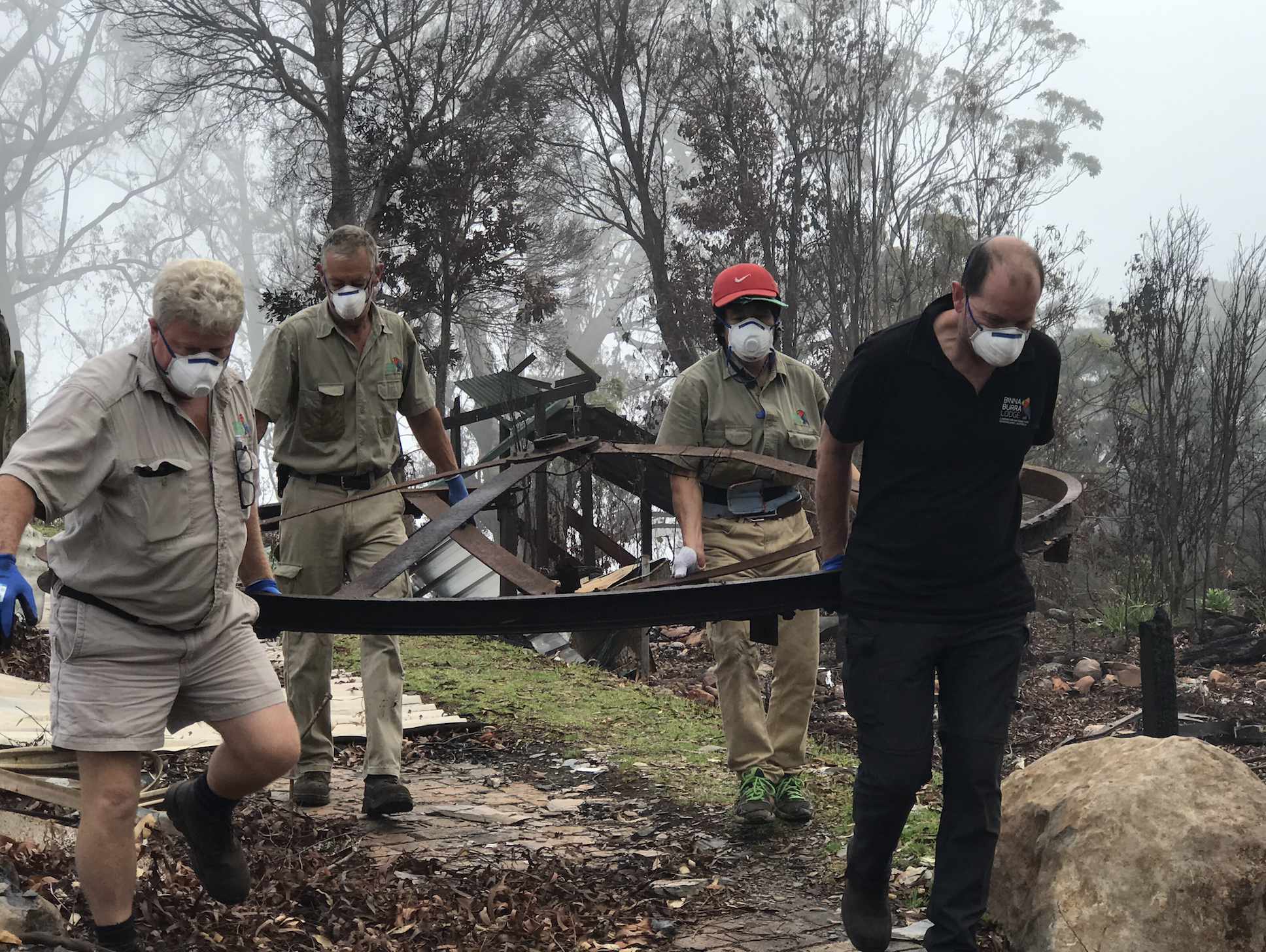 Ian Pritchard (in black) leads a rescue of a large metal wheel that was originally laid horizontally on the western side of the Lodge site. Photo: Binna Burra Lodge
